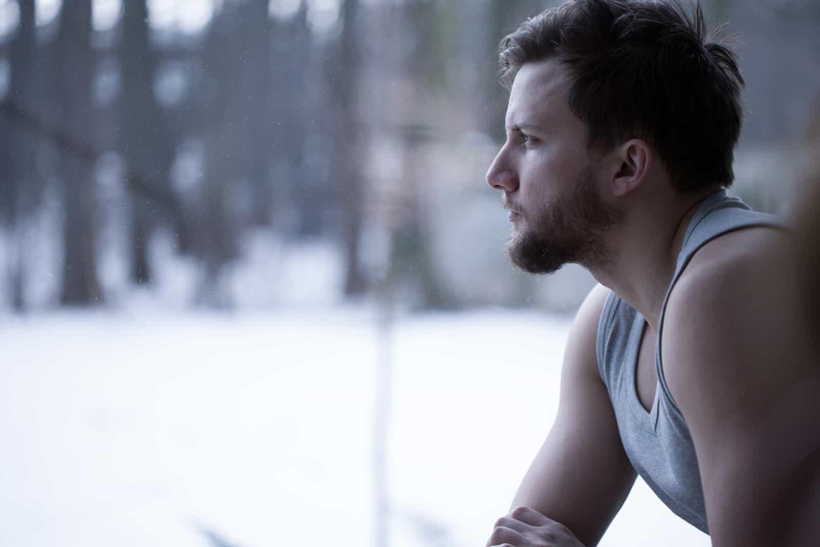 Mann, der durch das Fenster schaut und nachdenkt