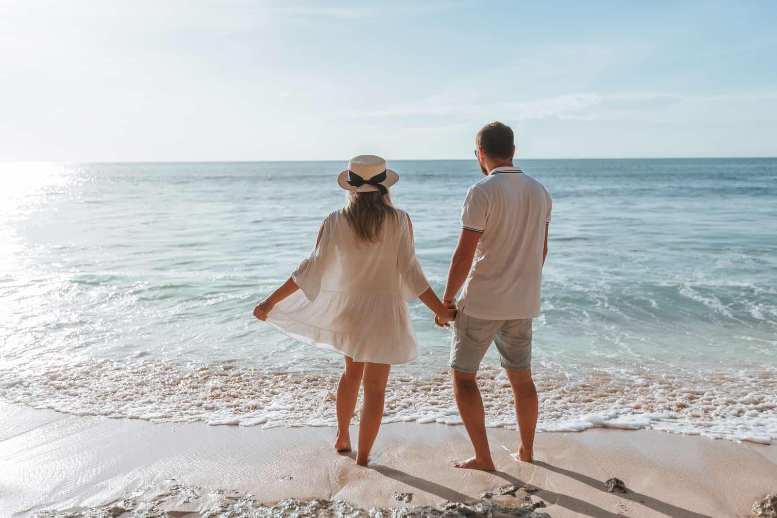 Mann und Mädchen halten sich an den Händen und beobachten den Sonnenuntergang am Strand
