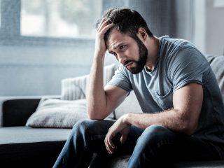 Trauriger unglücklicher gutaussehender Mann, der auf dem Sofa sitzt