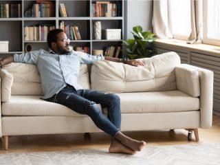 junger Mann sitzen entspannen auf bequemer Couch im Wohnzimmer