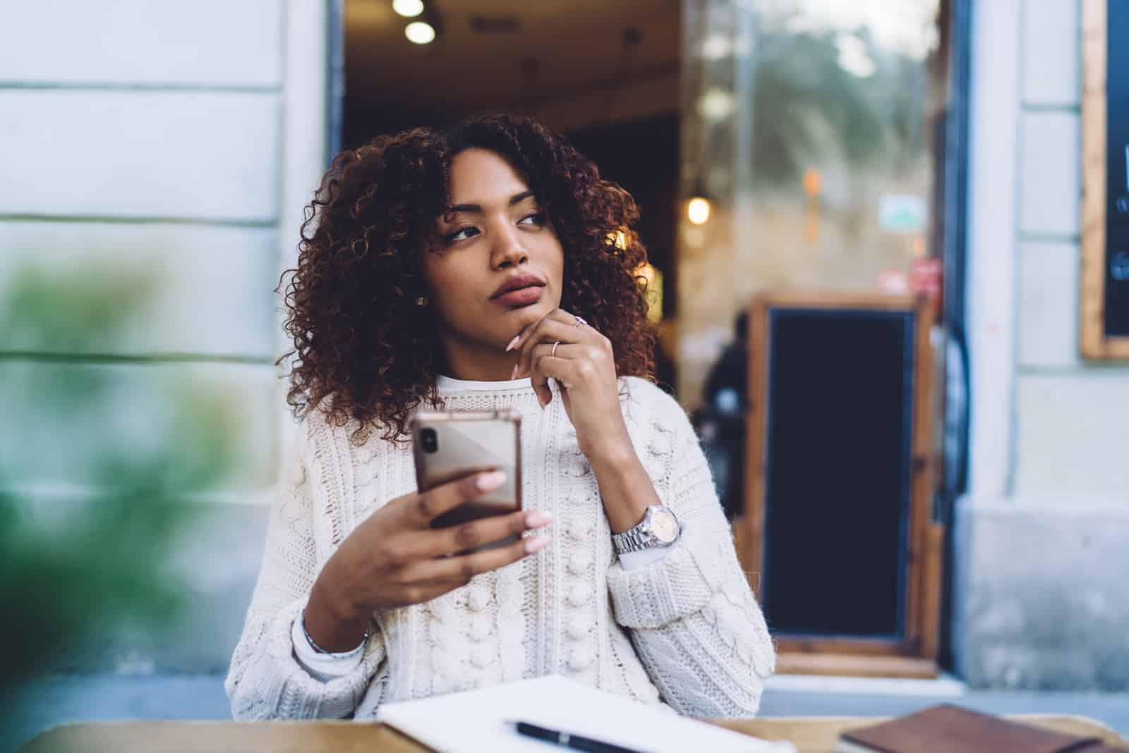 Nachdenkliche Frau in Freizeitkleidung, die am Holztisch sitzt