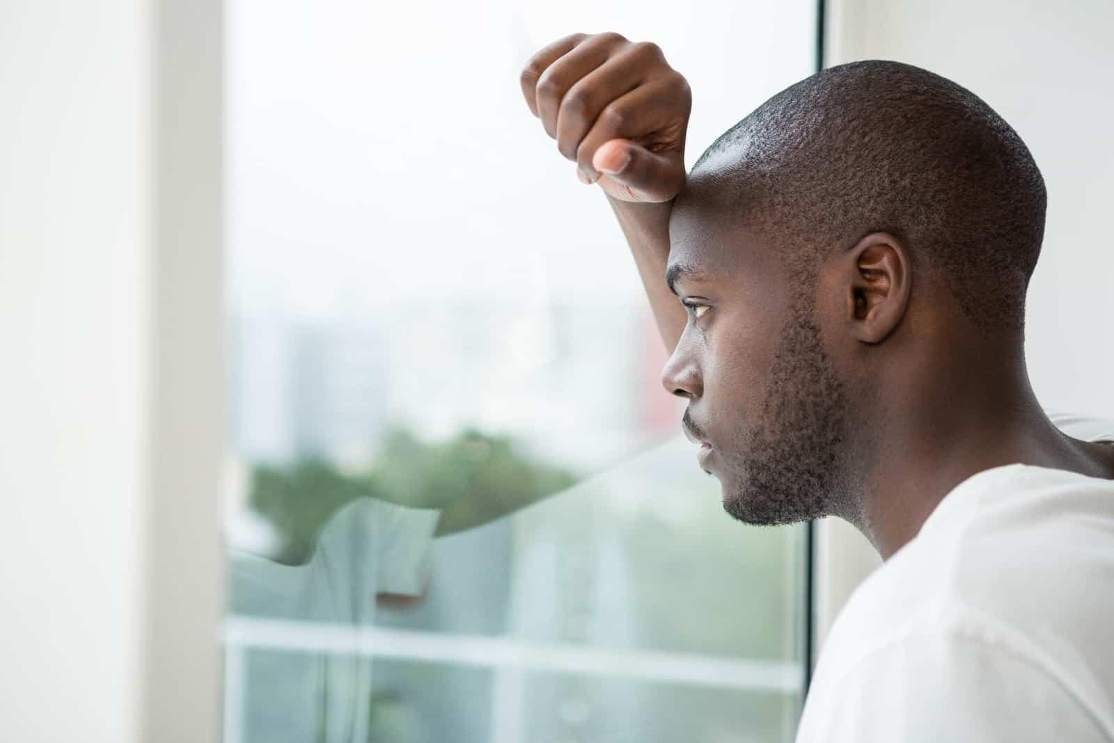 Nachdenklicher Mann, der aus dem Fenster im Schlafzimmer zu Hause schaut