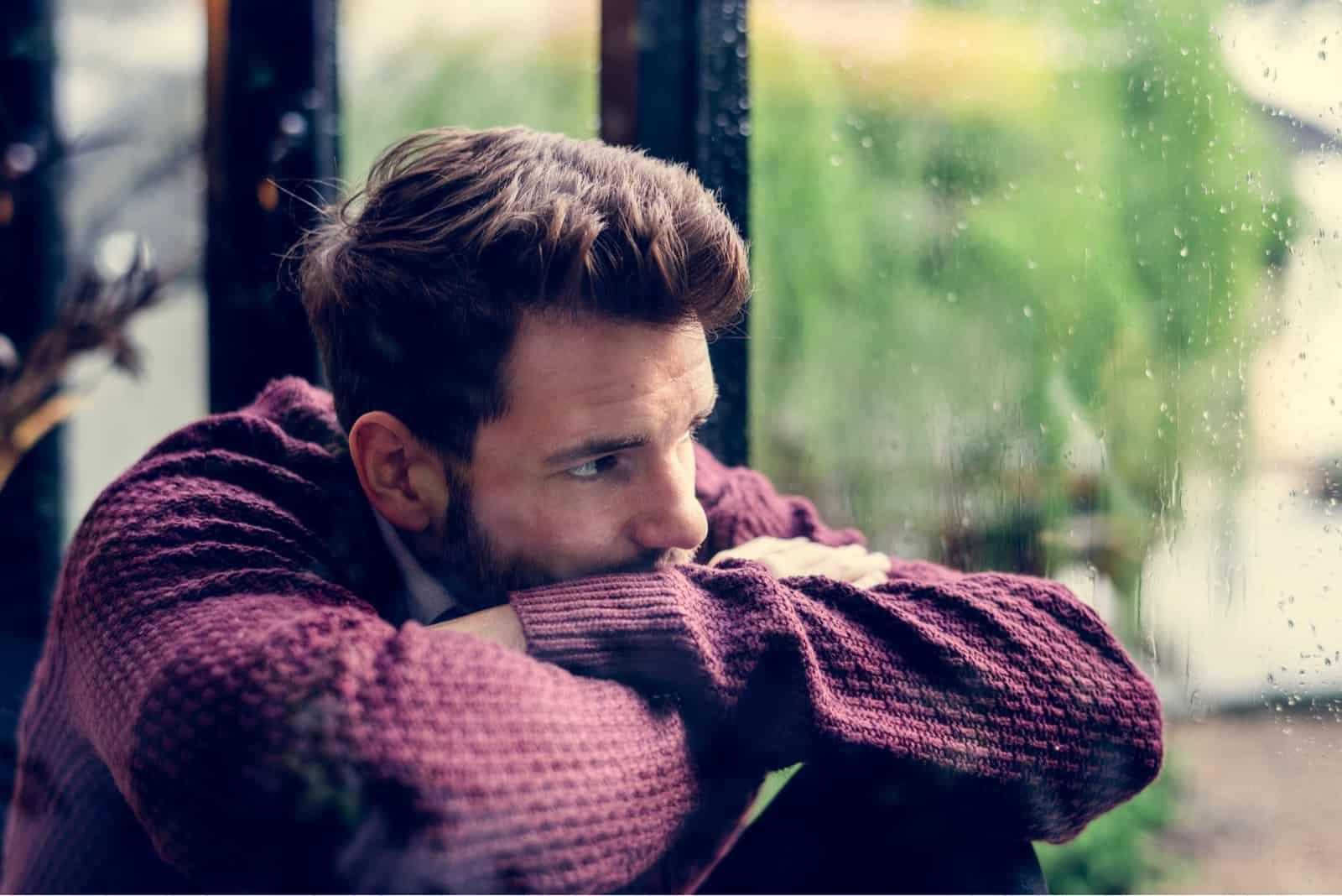 Nachdenklicher Mann, der aus dem Fenster schaut