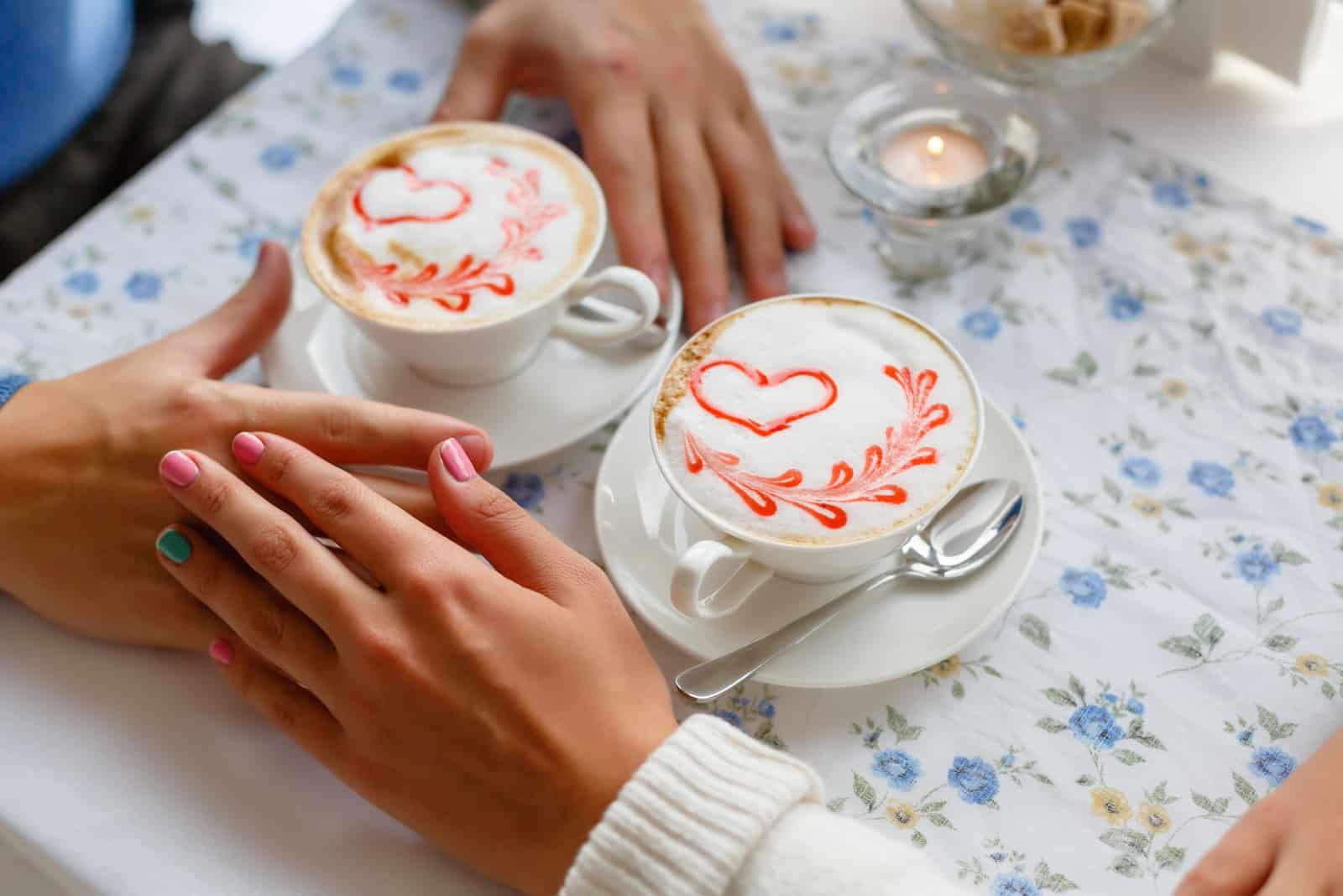 Paar trinken Kaffee in Liebe und verschränken die Hände über den Tisch im Café