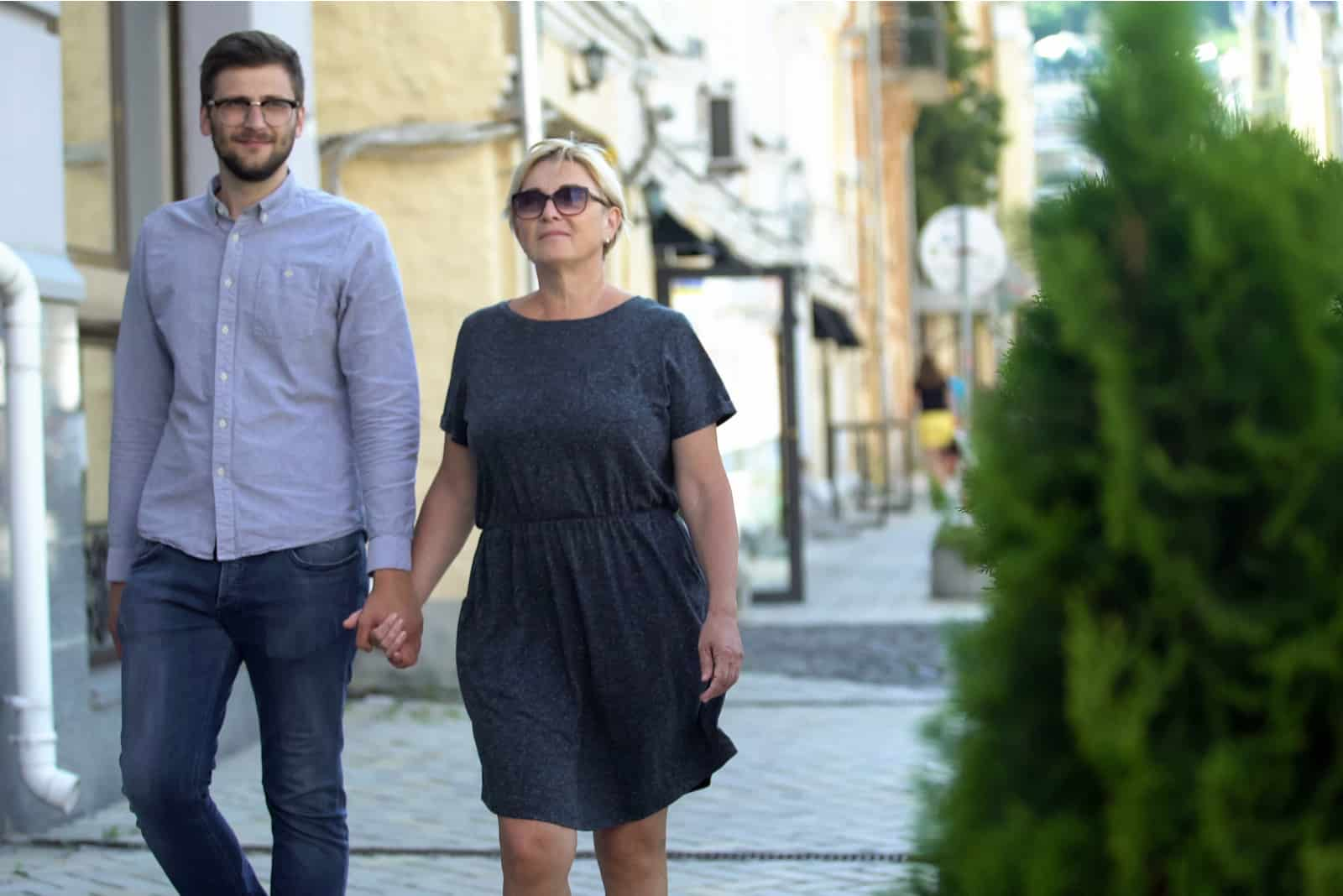 Reife Frau, die auf Straße mit jüngerem Mann geht