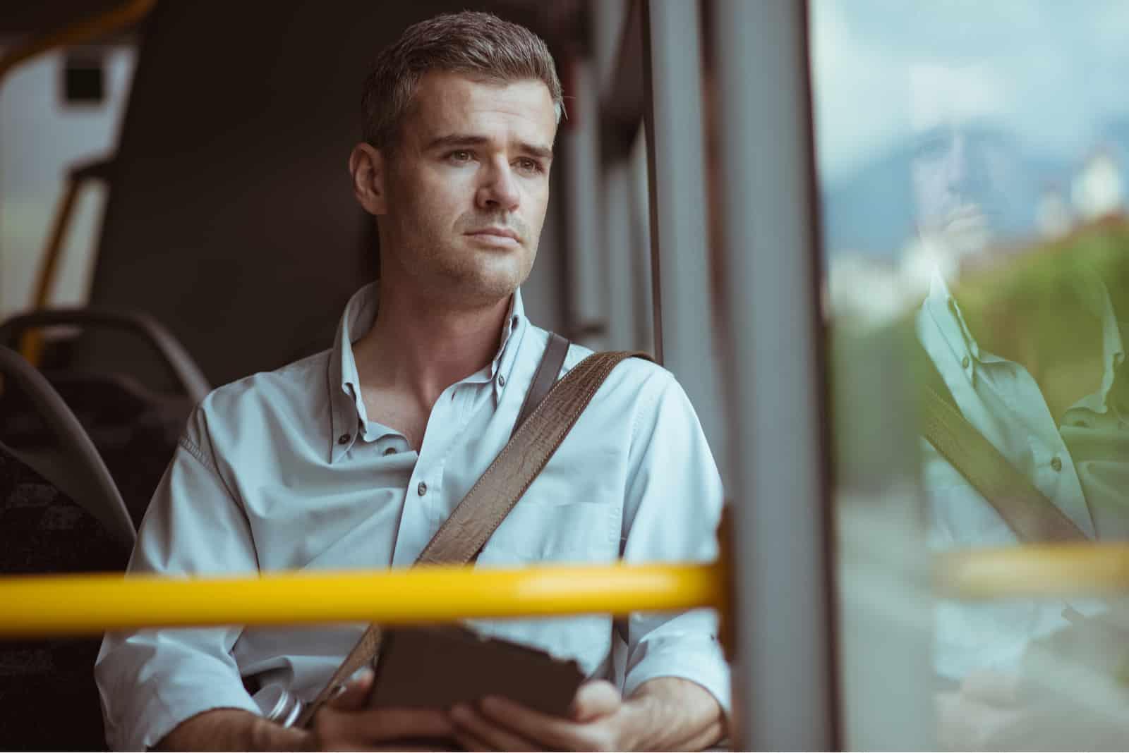 Selbstbewusster nachdenklicher Mann, der im Bus sitzt