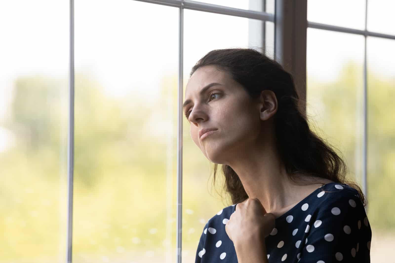 Unglückliche junge kaukasische Frau schauen in Fensterentfernung