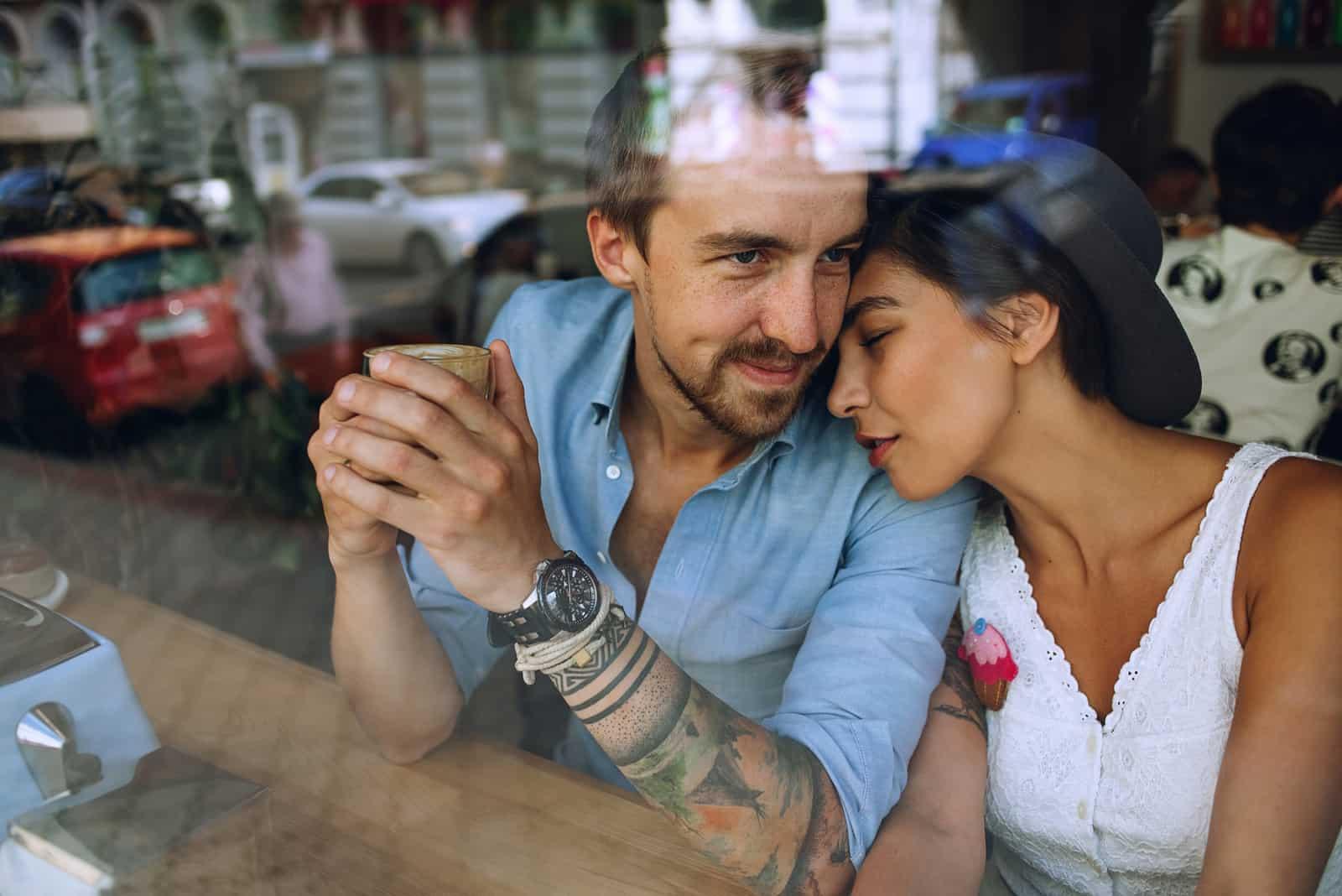 Verträumtes Paar, das sich am sonnigen Tag im Café hinter dem Fenster ausruht?