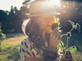 Mädchen riecht Sonnenblume in der Natur