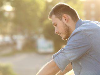 Ein trauriger Mann, der auf einen Balkon hinunterblickte