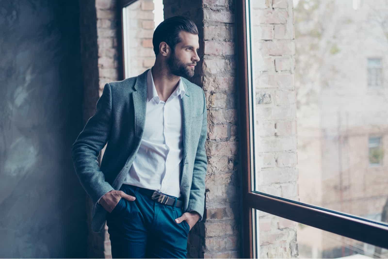 bärtiger Mann steht am Fenster