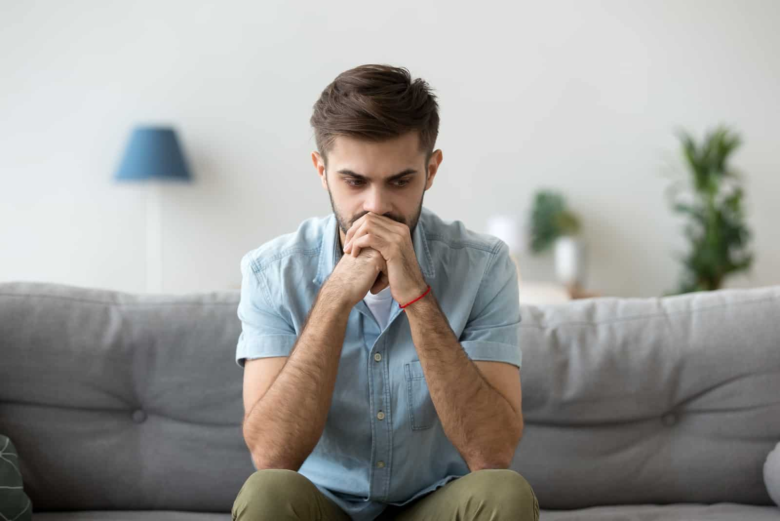 ernsthafter Mann, der allein auf der Couch zu Hause sitzt
