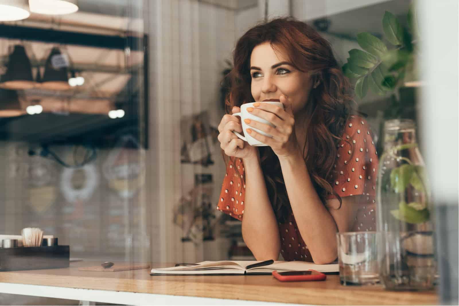 junge Frau, die Kaffee am Tisch mit Notizbuch im Café trinkt