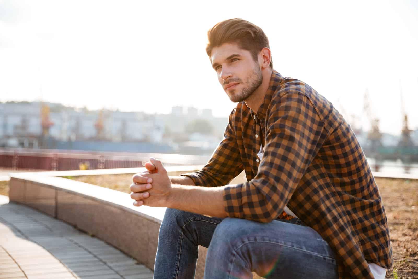 junger Mann im karierten Hemd, der draußen sitzt und denkt