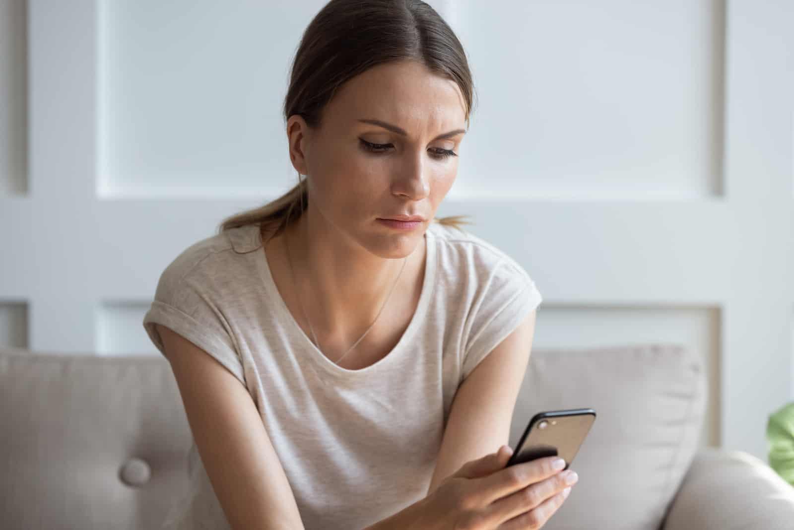 nachdenkliche Frau, die Handybildschirm betrachtet