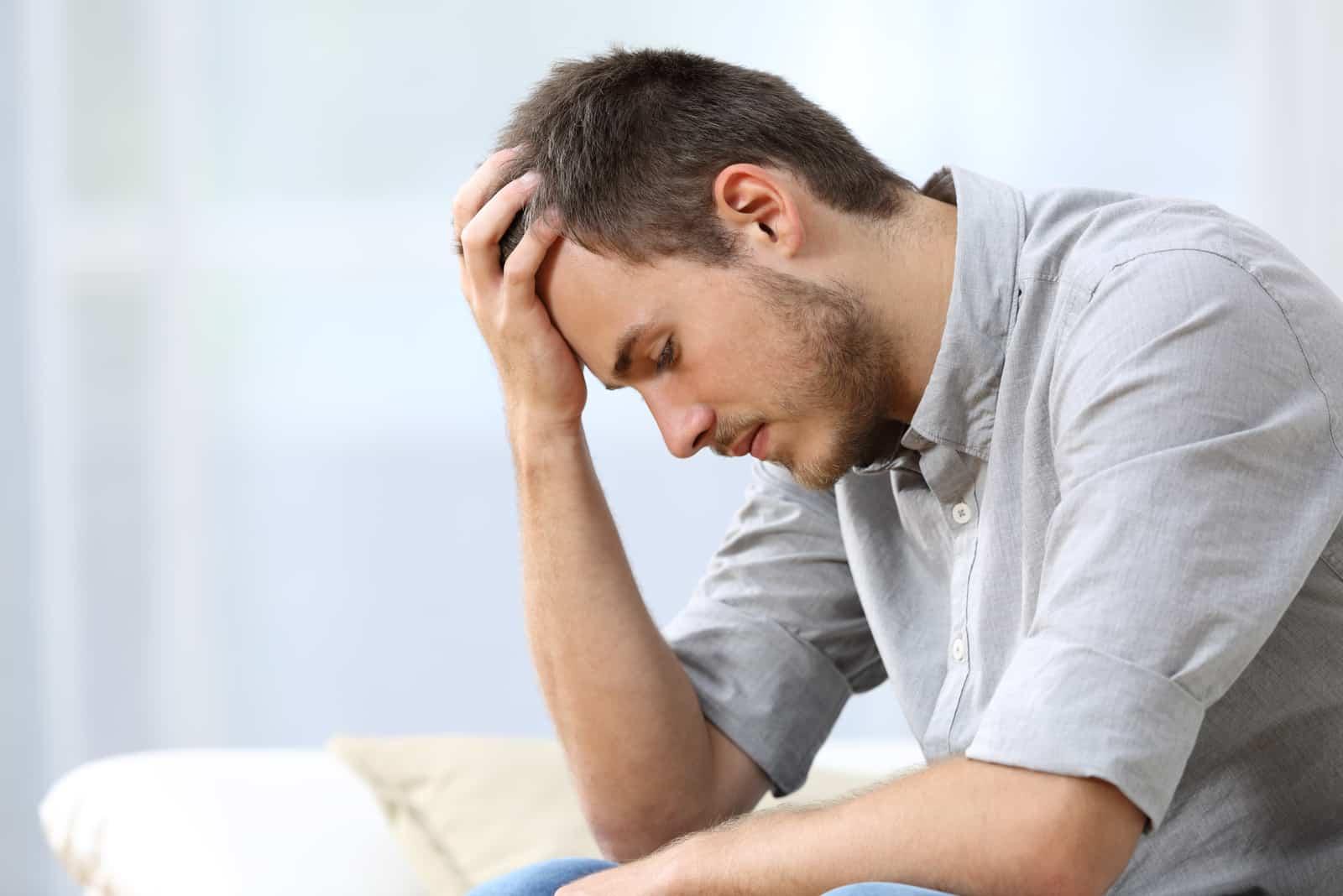 trauriger Mann mit einer Hand auf dem Kopf, der auf einer Couch sitzt