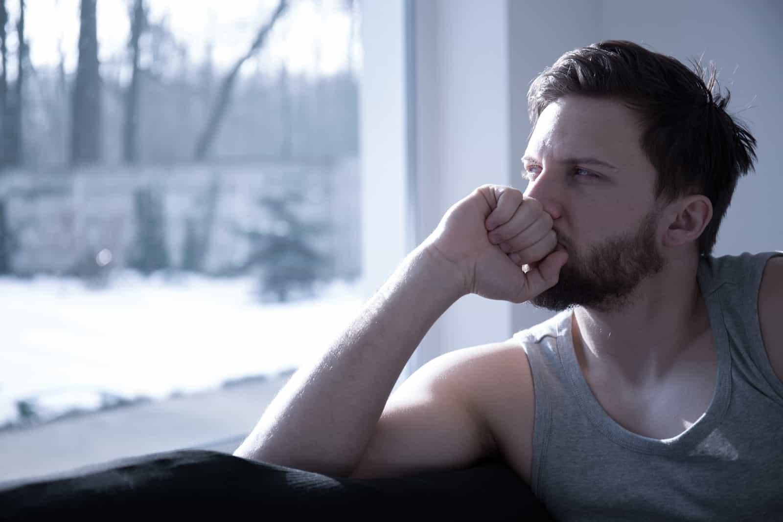 unglücklicher gutaussehender Mann, der am Fenster sitzt