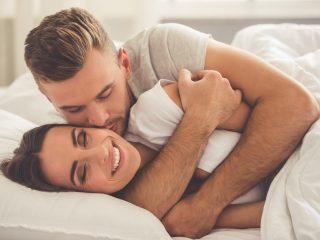 junger Mann umarmt und küsst seine schöne lächelnde Frau