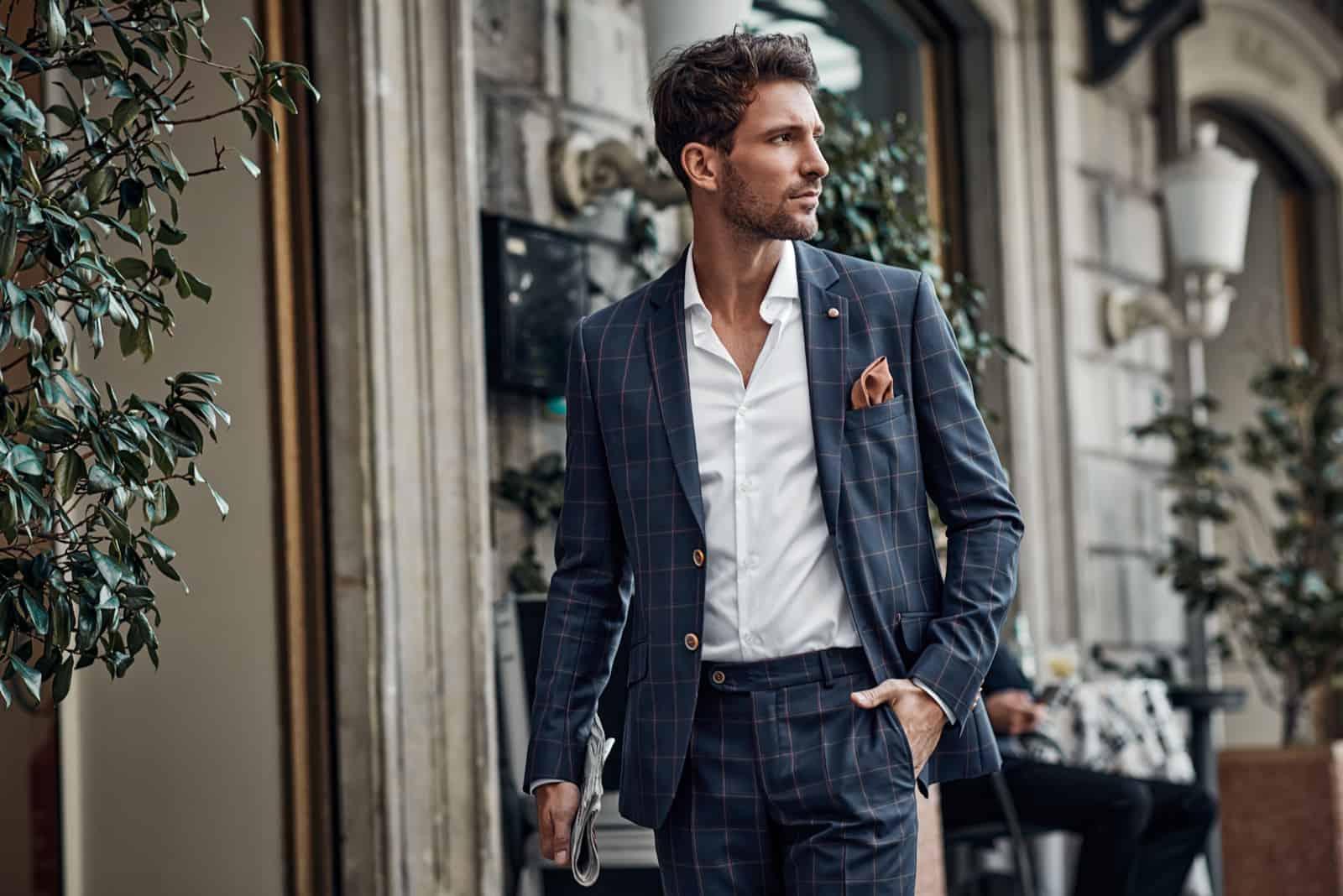 Hübsches männliches Model im karierten Anzug, das auf die Straße geht