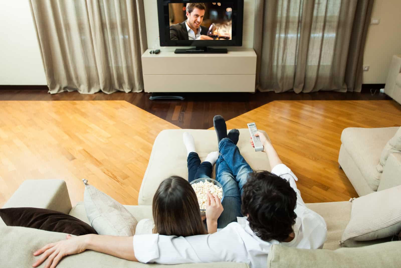 Junges Paar isst Popcorn, während es einen Film sieht