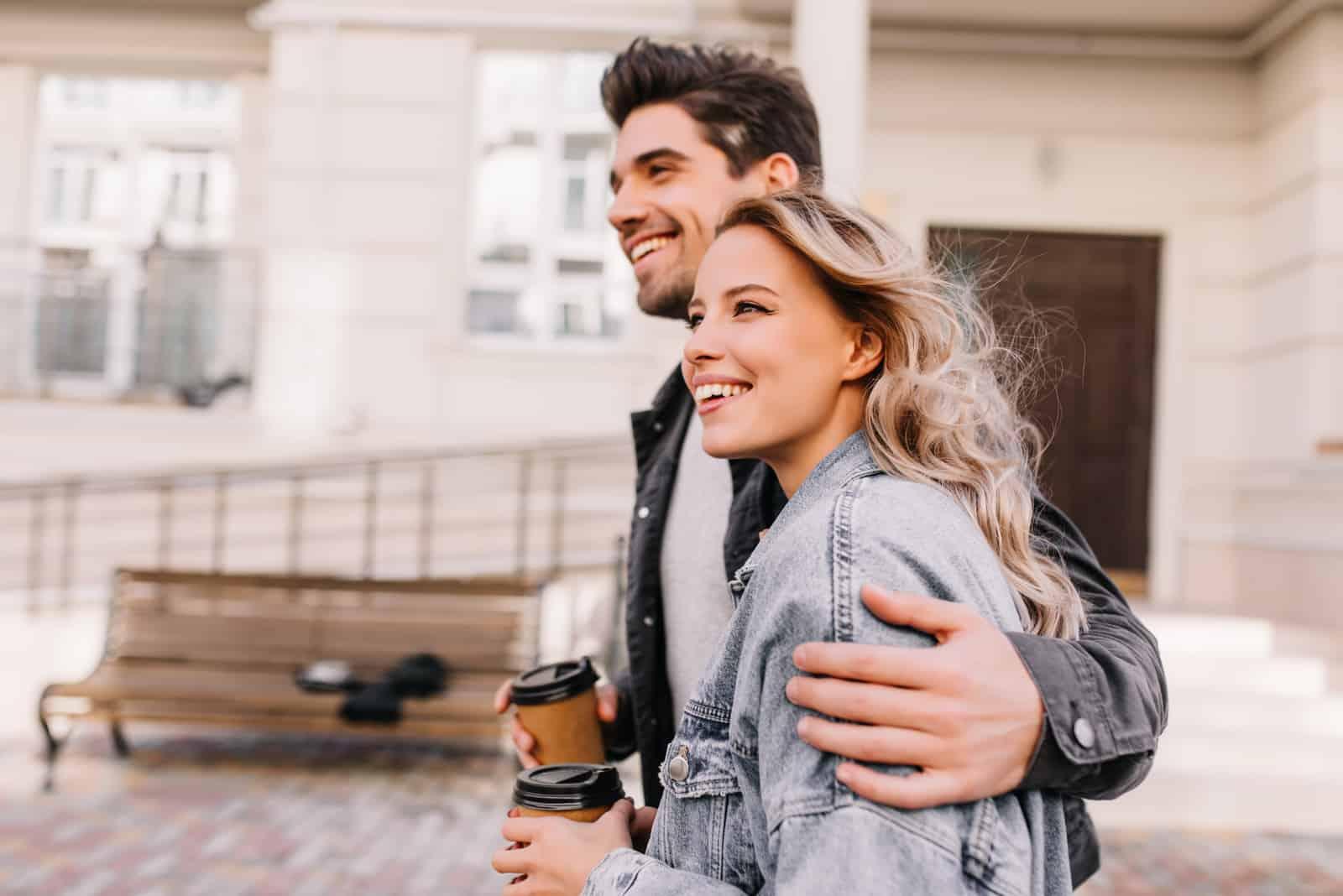 Mädchen trinkt Kaffee beim Spaziergang mit ihrem Freund