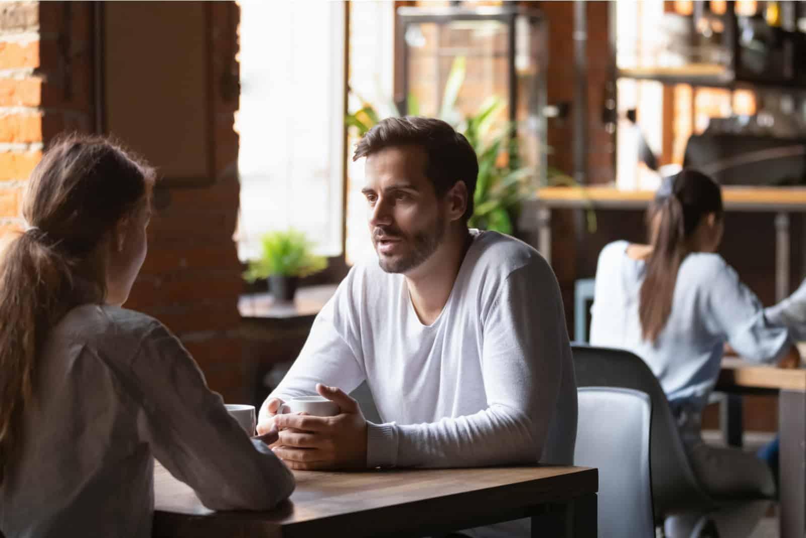 Paar sitzt am Cafétisch und trinkt heißen Kaffee hot