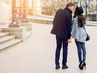 junges Paar, das auf europäischen Herbststraßen spaziert