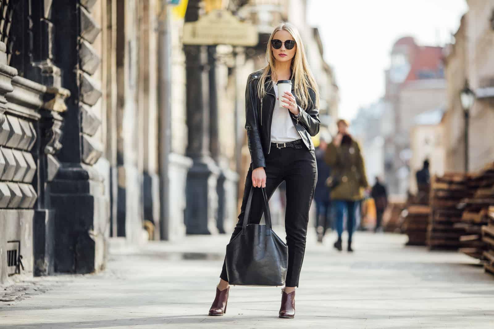 hübsches Mädchen geht mit einer Tasse Kaffee auf die Straße