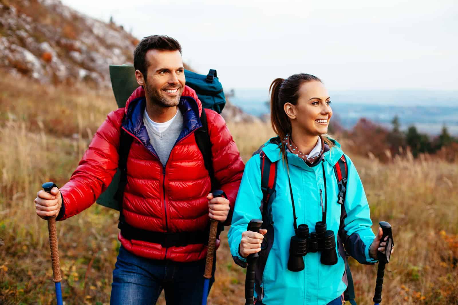 Backpacker-Paar wandert im Herbst mit Stöcken