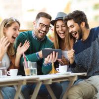 Freunde sitzen da und schauen sich etwas auf dem Tablet an und lachen