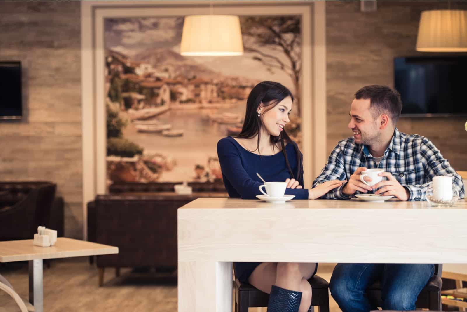 Ein Mann und eine Frau sitzen an einem Tisch und unterhalten sich