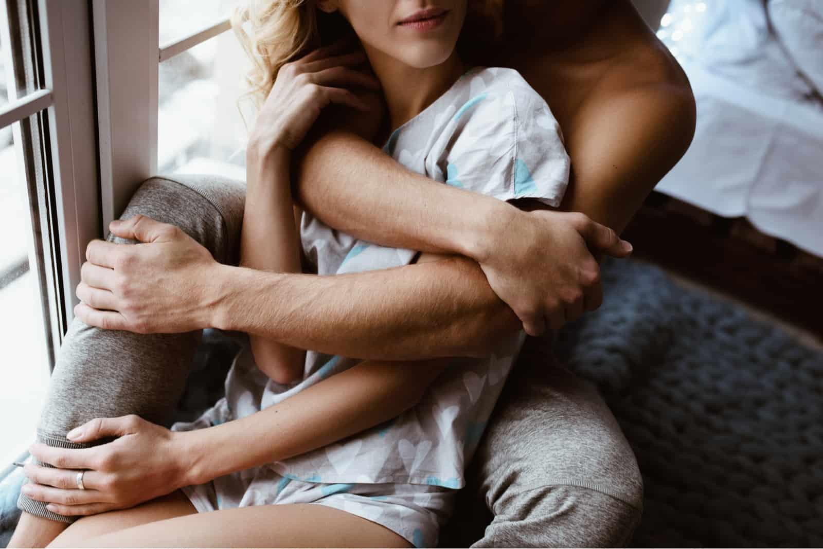Ein Paar umarmt sich am Fenster