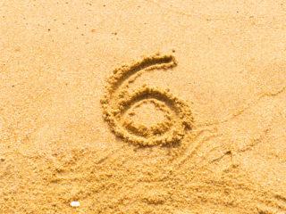 eine Zahl in den Sand gezeichnet