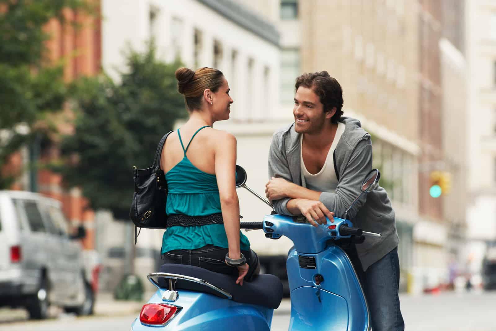 Frau auf Moped im Gespräch mit Mann auf der Straße