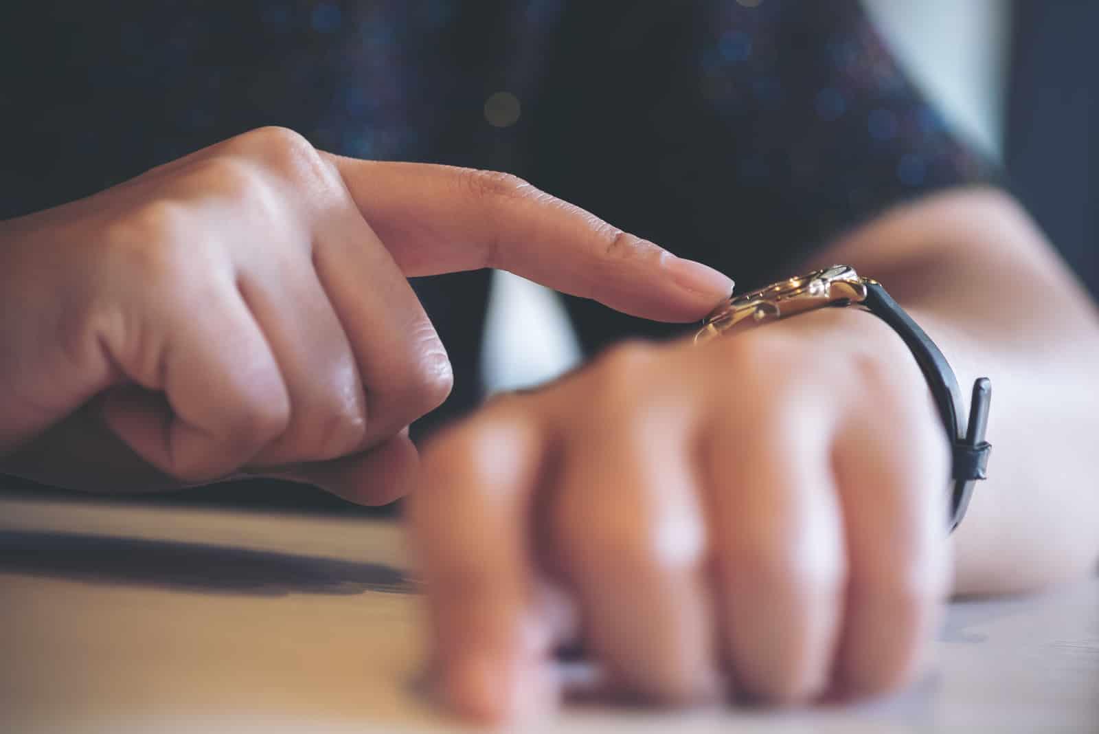 Frau zeigt auf eine schwarze Armbanduhr