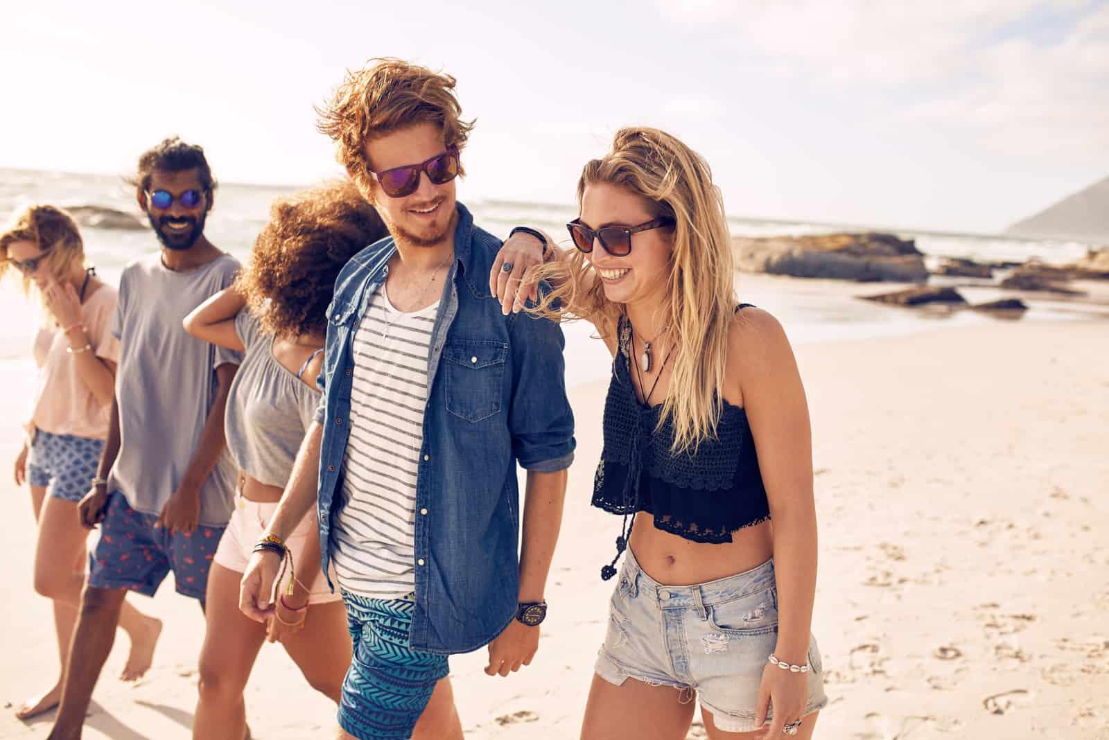 Freunde gehen am Strand entlang