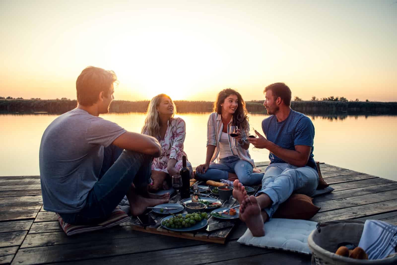 Freunde sitzen auf dem Pier und reden