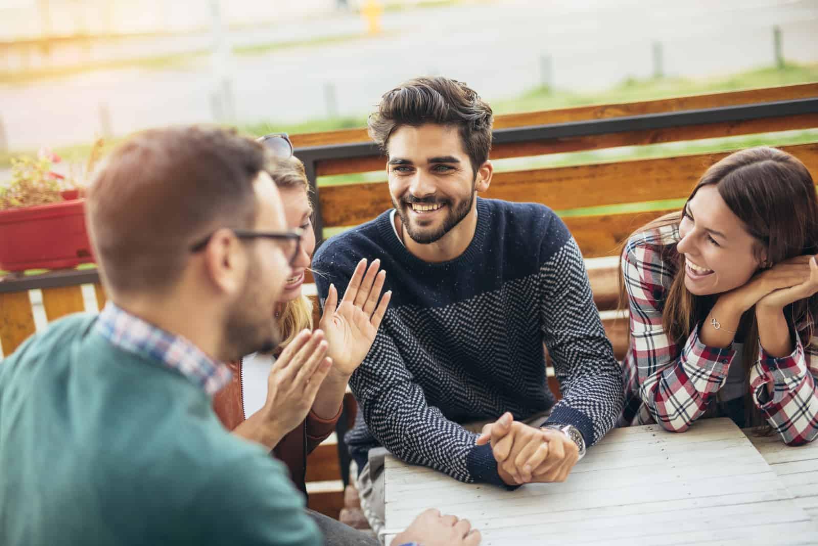 Freunde sitzen draußen an einem Tisch und unterhalten sich