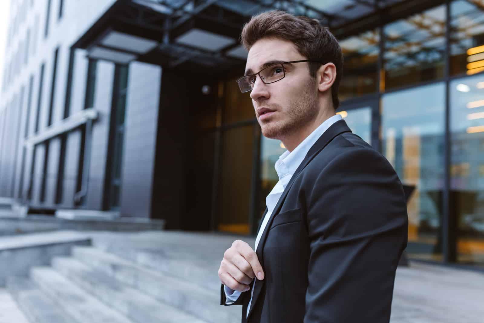 Geschäftsmann in Anzug und Brille seitlich stehend