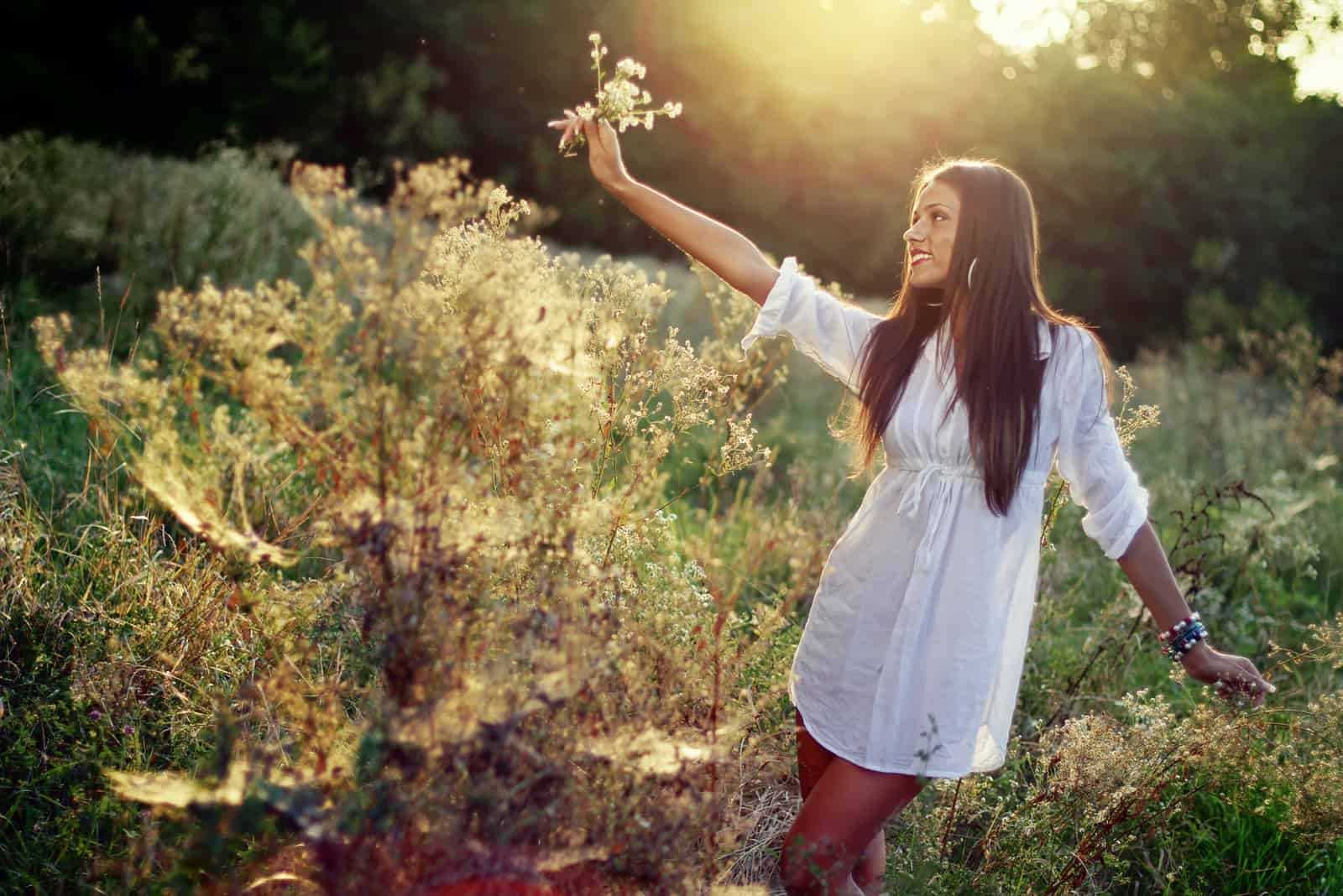Glückliches brünettes Mädchen, das sich bei Sonnenuntergang auf dem Feld entspannt