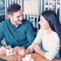 Ein Mann und eine Frau sitzen in einem Café und unterhalten sich beim Kaffee