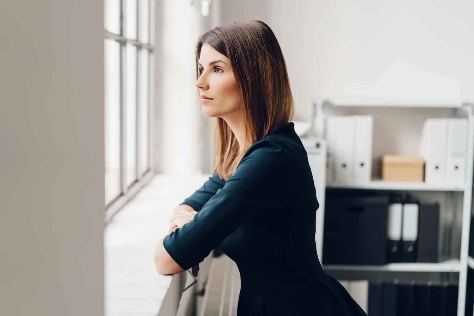 Hübsche Frau, die aus einem Fenster starrt