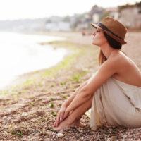 Ruhige Frau, die allein an einem Sandstrand am Abend sitzt