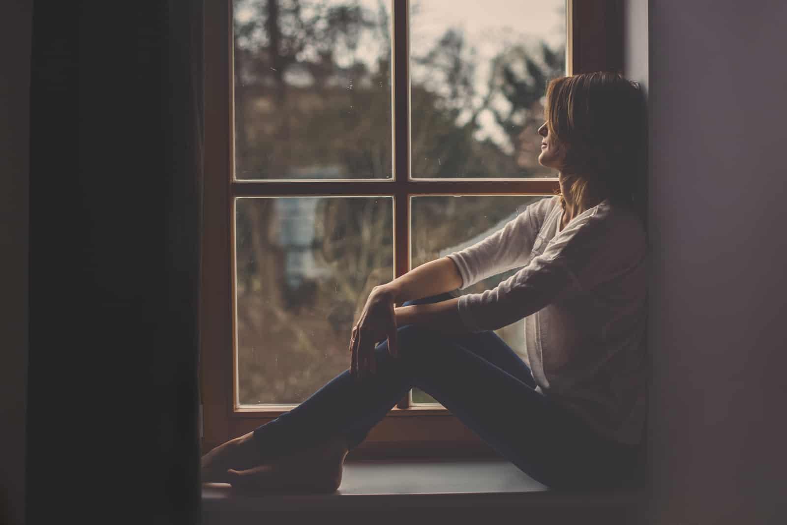 Junge attraktive Frau, die auf einem Fenster sitzt