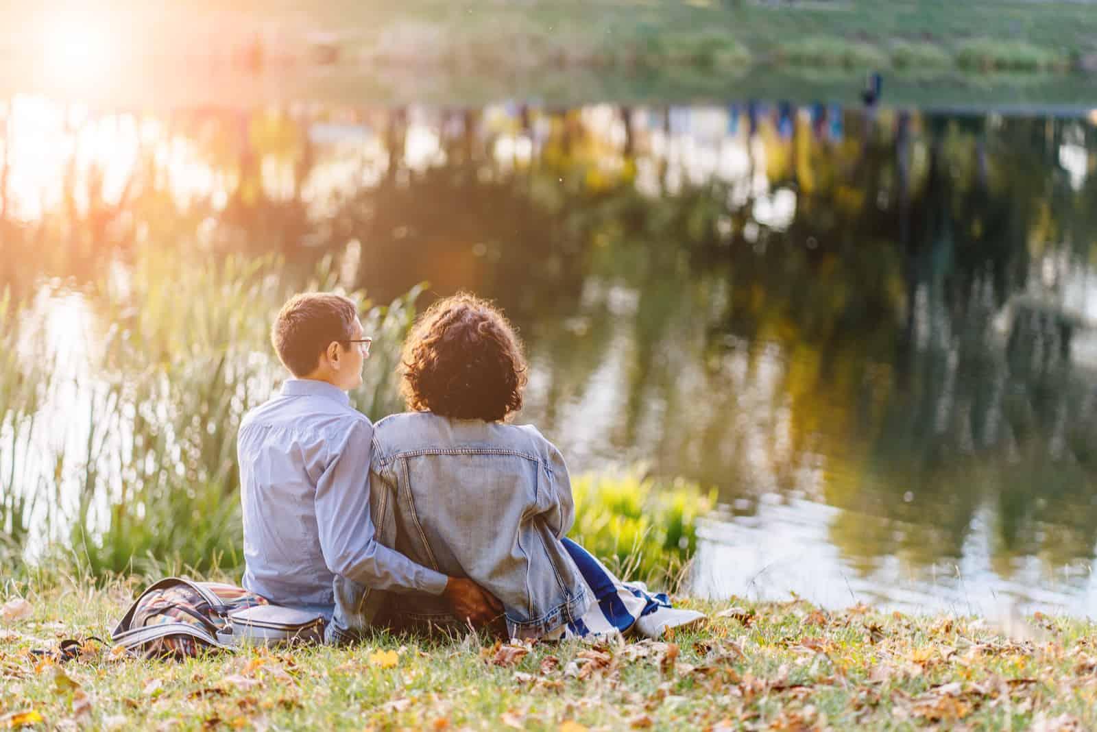 Liebespaar umarmt am Ufer des Sees sitzen