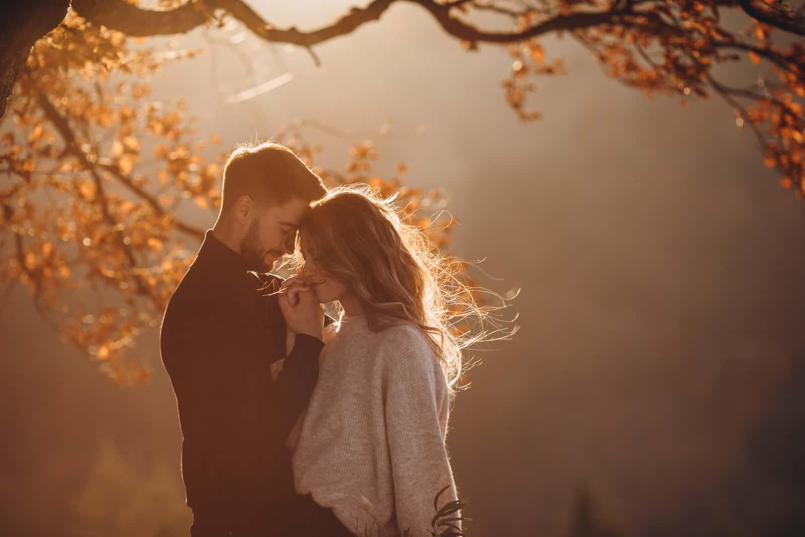 Mann und ein Mädchen umarmen sich zusammen unter einem großen alten Baum