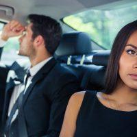 Geschäftsmann und Geschäftsfrau reiten auf dem Rücksitz im Auto