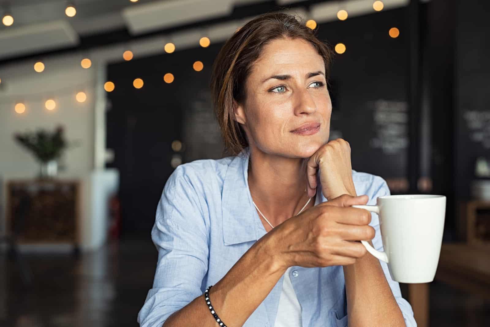 Nachdenkliche reife Frau, die in der Cafeteria mit Kaffee sitzt holding