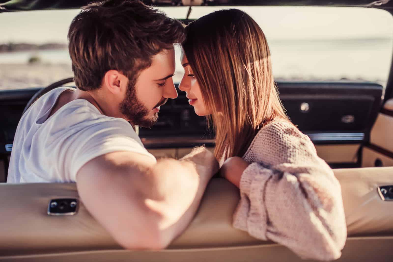 Romantisches Paar sitzt im grünen Retro-Auto am Strand