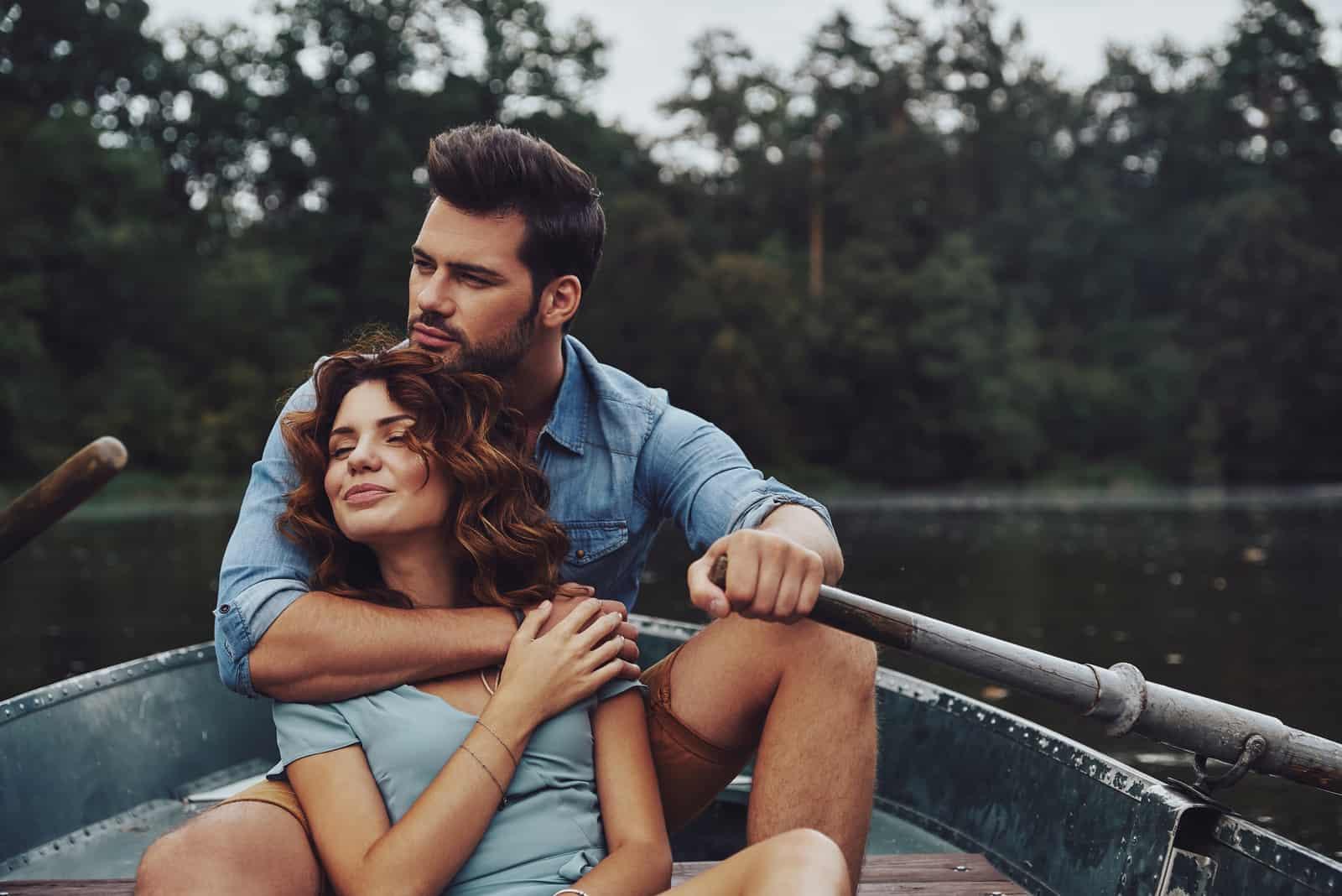 Schönes junges Paar, das sich umarmt und wegschaut, während es ein romantisches Date auf dem See genießt